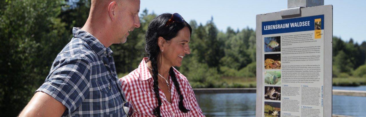Westallgäuer Wasserwege Wanderer an der Wandertafel am Waldsee in Lindenberg.