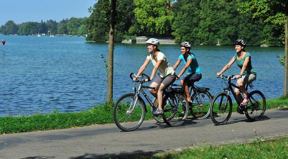 Radfahren am Bodensee mit Blick auf den See und drei Radlerinnen