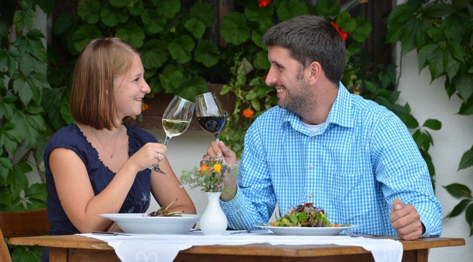 Genussregion Westallgäu Pärchen am Tisch mit Weingläsern